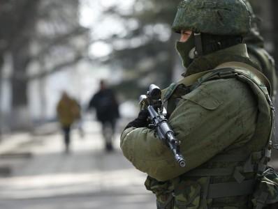 An armed man patrols near the regional parliament building in the Crimean city of Simferopol