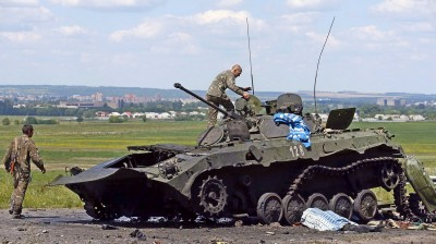 Ukrainian soldiers check a destroyed armoured vehicle at a Ukrainian Army checkpoint in the outskirts of the eastern Ukrainian town of Slaviansk